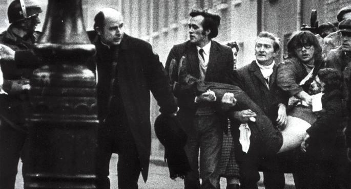 1972an Derryn izan zen tiroketaren irudi ezaguna: Edward Daly apaiza (zapi zuria eskuan duela) eta beste batzuk, herioan den 17 urteko mutikoa lagundu nahian.