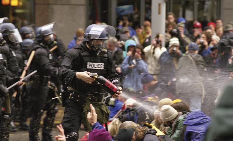 MMEren aurkako protestak Seattlen, 1999ko azaroaren 30ean. Polizia manifestarien kontra piperbeltz espraia botatzen. (Arg: Steve Kaiser)