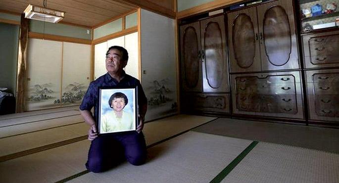Hamako Watanaberen alarguna, Mikio Watanabe, emaztearen argazkia eskuetan duela.