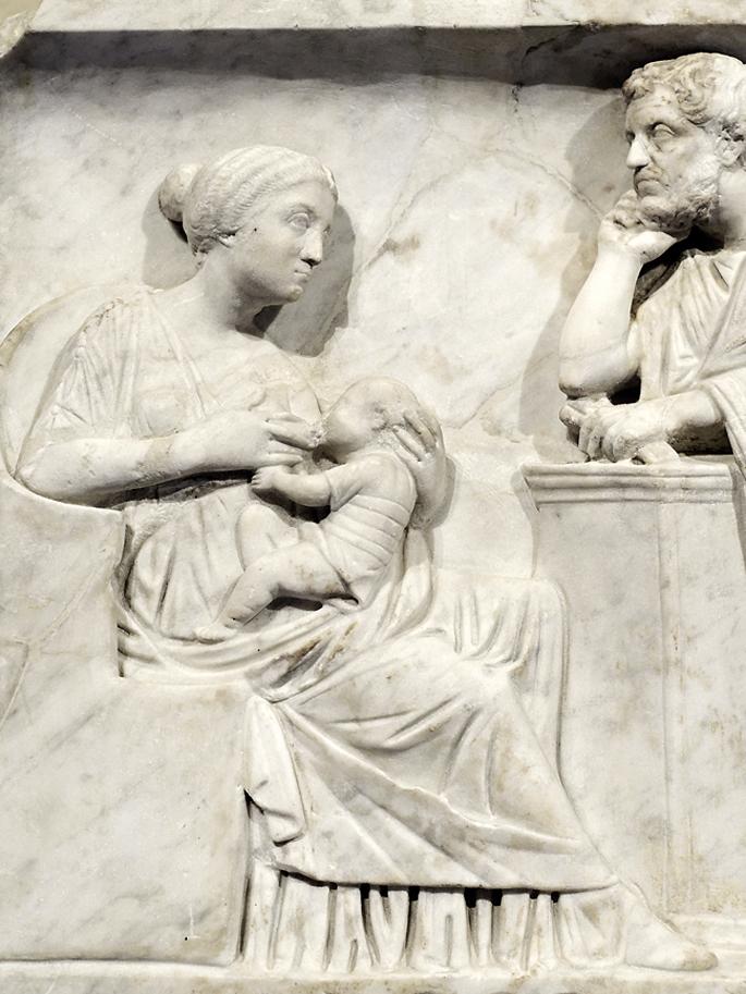 Ama haurrari bularra ematen, aitaren aurrean. Haurtzaroan hildako erromatar baten sarkofagoko erliebeen xehetasuna (K.a. 150 inguruan).