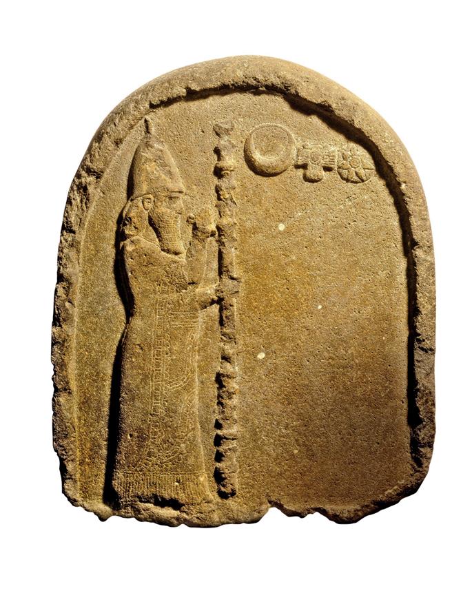 Estela honetan Nabonidok errege babiloniarren jantzi tradizionala du soinean, eta zeremonia zetroa eskuetan. Alboan Sin, Ishtar eta Shamash jainkoen sinboloak ageri dira. Lehenaren kultua inposatzeagatik herritarren babesa galdu zuen Babiloniako azken err