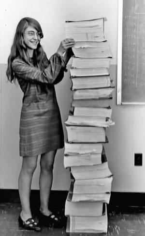 Margaret Hamilton ingeniaria, alboan AGCren edo Apollo ontzia gidatzeko ordenagailuaren iturri-kodea inprimatuta duela. Fisikoki, kodea ez zen bi metrora iristen. Birtualki, paper mordo hark ilargiraino eraman zuen gizakia.