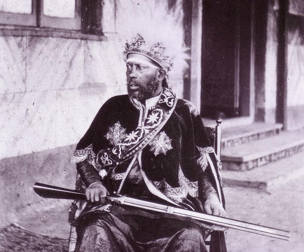 Etiopiako enperadore Menelik II.a (1844-1913) lehoi ilez egindako koroa buruan eta erriflea eskuetan, herrialdeko buru militarra ere bazela azpimarratzeko.