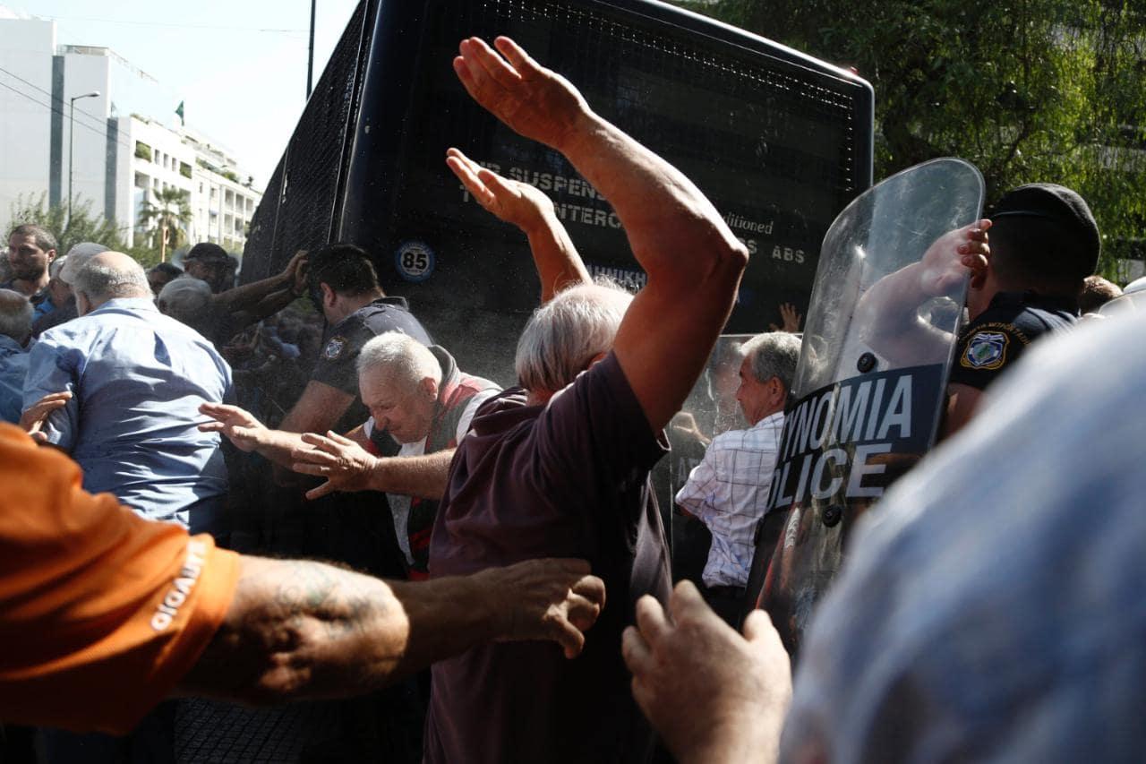 Petros Giannakourisen argazkian, zahar jendea poliziarekin borrokan Atenasen, berrikitan pentsioen murrizketengatik haserre egindako protesta batean. Irudian ikus daitezke zaharretako batzuk polizien autobusa uzkailtzeko ahaleginean. Troikaren planak derr