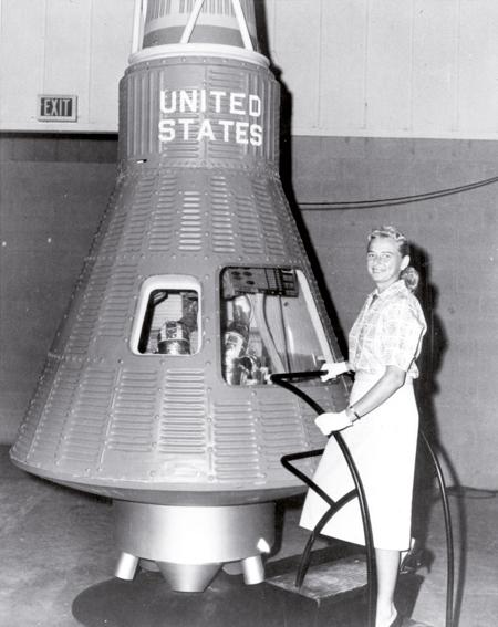 Jerrie Cobb pilotua Mercury proiektuko espazio-kapsularen alboan. Cobbek astronauta izateko proba fisiko eta mediko guztiak gainditu zituen, FLAT programako beste emakume batzuek bezala. Baina ez zieten espaziora joateko aukerarik eman. (Arg.: NASA)