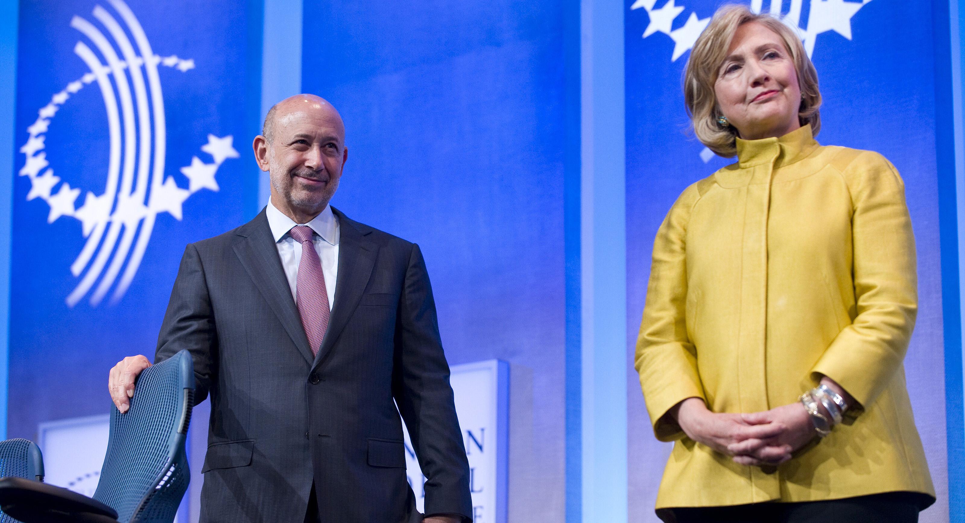 """Politico hedabidetik hartutako argazkian Hillary Clintonen ondoan Lloyd Blankfein Goldman Sachs bankuko buru nagusia. Berea bezalako finantza erakundeek eragindako krisi betean esan zion kazetariari: """"Ni ez naiz bankero bat baizik, Jainkoaren lana egitera"""
