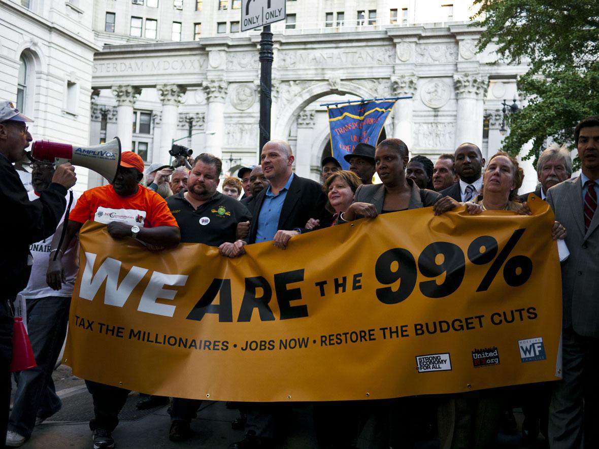 """'The 4th Media' hedabidearen argazkian,  Occupy Wall Streeten manifestazio bat Washingtonen 2012an. Afixan aldarrikatzen dute """"Geu gara %99a"""" eta eskatzen milioidunei zergak ezarri, lanpostuak sortu eta aurrekontuak murrizketak baino lehenagoko egoerara"""