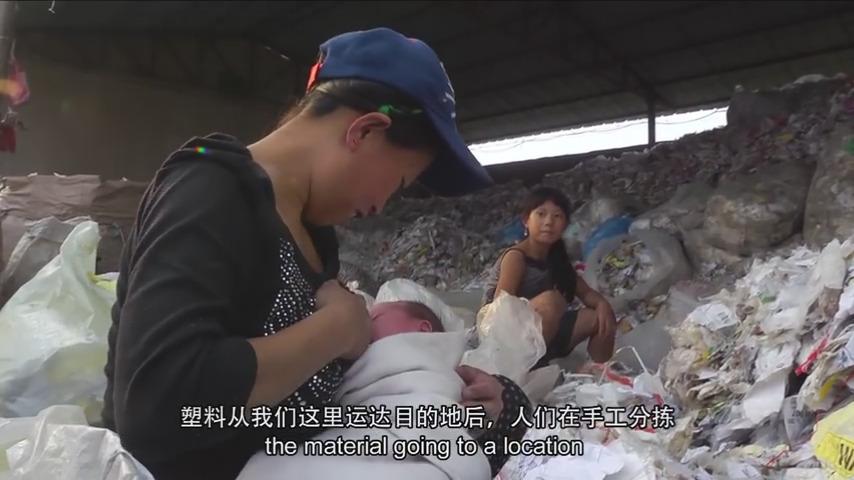 'China Plastics' dokumentaletik ateratako irudian, protagonistetako bat den Ji-Jie neskatoak plastiko nahasien pila gainetik begiratzen die bere amari eta honi bularra hartzen dion ahizpa txikiari. 11 urterekin egunero ari dira lanean ama-alabak Txinako b