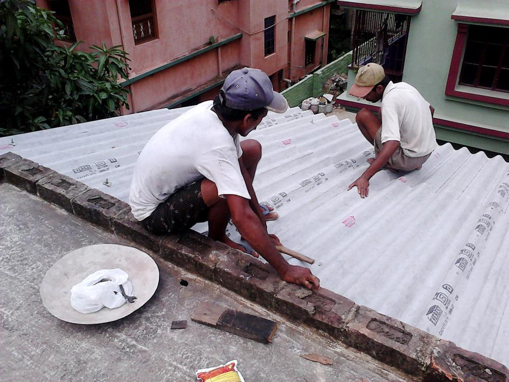 Indian amiantoz egindako teilatua jartzen 2011n. Everest Asbestos Cement irakur daiteke teilen itsasgarrietan, egun abestoarekin lan egiten duen enpresa ugarietako bat. (Arg.: Wikimedia Commons)