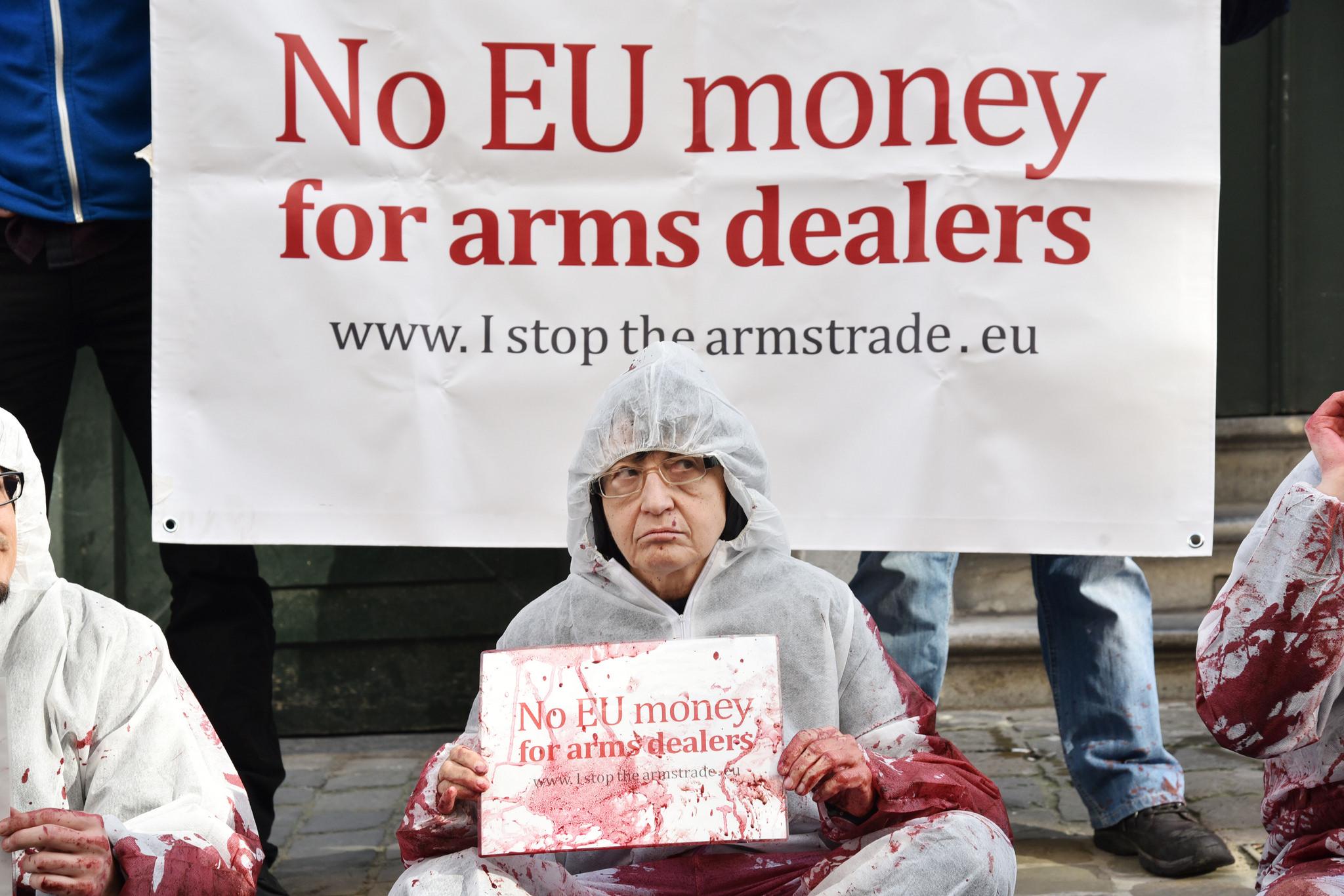 """I Stop the Arms Trade [Ni ere Arma Salerosketa Geldiarazten] erakundeak zabaldutako irudian, ekintzaile bat odol koloreko tintaz zikindua: """"Europar Batasunaren dirurik ez arma saltzaileentzat"""" dio atzeko afixak. Europak, estatuek eta baita gobernu autonom"""