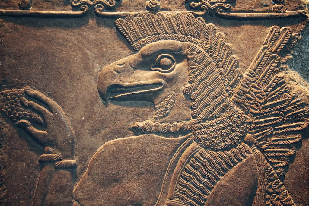 Nisroch jainko asiriarra landareak bedeinkatzen ageri da erliebe honetan, baina haren iragana bihurriagoa izan zen: sexua bultzatzen zuen deabrua zen. (arg: British Museum)