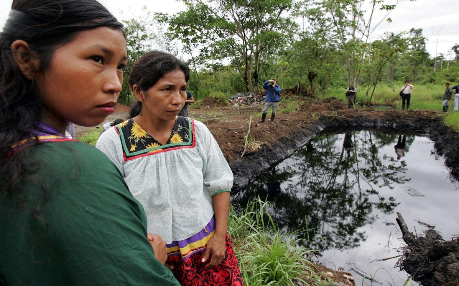 'Aljazeera'-k zabaldutako argazkian, Sucumbios probintziako herritar batzuk  Texaco-Chevronek petrolioz eta hura lurpetik erauzteko toxikoz kutsatutako aintzira baten ondoan. Amazonian multinazionalek kaltetutako herritarrok kexu dira Rafael Correaren or
