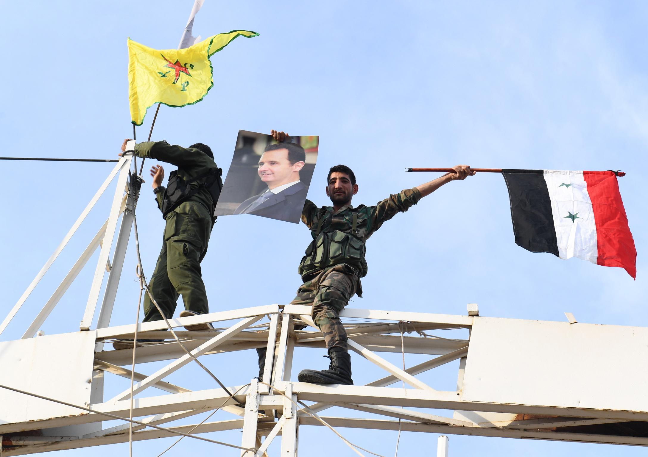Kobanen, soldadu siriarrak beren bandera eta Assaden erretratoa erakusten YPG kurduaren bandera horiaren ondoan.
