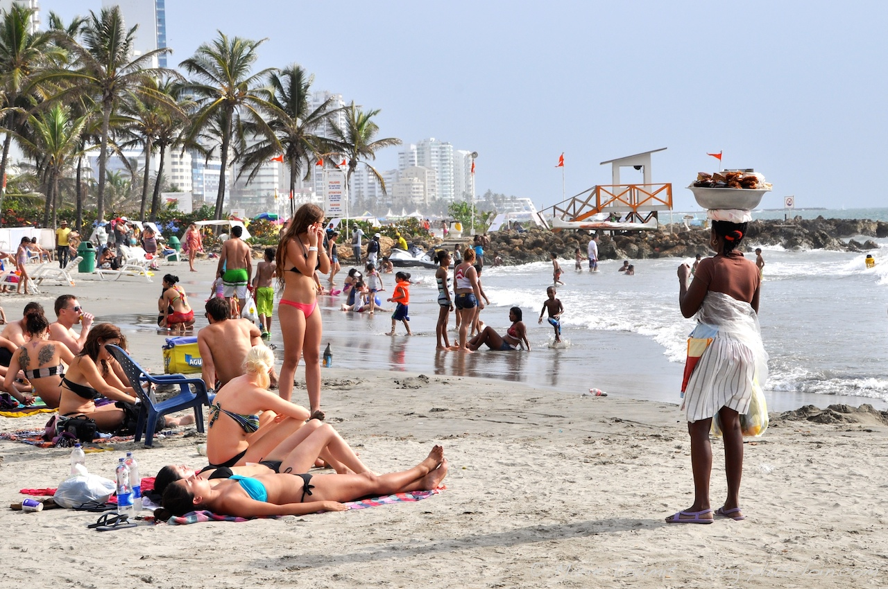 Turistei saltzen Kolonbiako Cartagena de indias hirian kaleko saltzaileak eguzkia hartzen ari diren jende aberatsen artean.