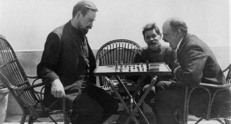Aleksandr Bogdanov idazlea (ezkerrean), aspertu samar dagoela dirudien Leninekin (eskuinean) xake partida jokatzen, Maxim Gorki (erdian) begira dutela.
